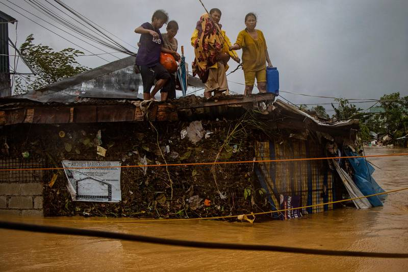 RODRIGUEZ, PHILIPPINES - NOVEMBER 12: Stranded residents wait to be rescued atop a roof as floodwaters continue to rise in a village, as Typhoon Vamco hits on November 12, 2020 in Rodriguez, Rizal province, Philippines. Typhoon Vamco has battered the Philippines causing widespread flooding and destruction in areas still reeling from the effects of Super Typhoon Goni. Authorities on Thursday have mounted several rescue operations as tens of thousands of homes have been submerged in floodwaters. Flights and mass transit in Manila were suspended, as well as work in government offices. (Photo by Ezra Acayan/Getty Images)