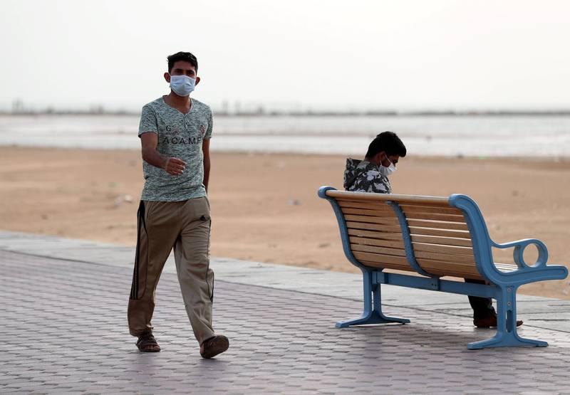 Ajman, United Arab Emirates - Reporter: N/A: Men wear a face masks in front of the beach in Ajman as a response to the Corona Virus. Monday, March 23rd, 2020. Ajman. Chris Whiteoak / The National