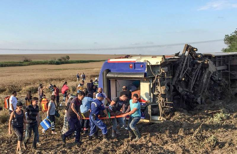 People and rescuers carry an injured woman after a train accident at Corlu district in Tekirdag, on July 8, 2018. Ten people were killed and 73 injured on July 8 when a train packed with weekend passengers derailed in northwest Turkey, sate-run TRT Haber television said, quoting the health ministry. - Turkey OUT  / AFP / DHA / DHA