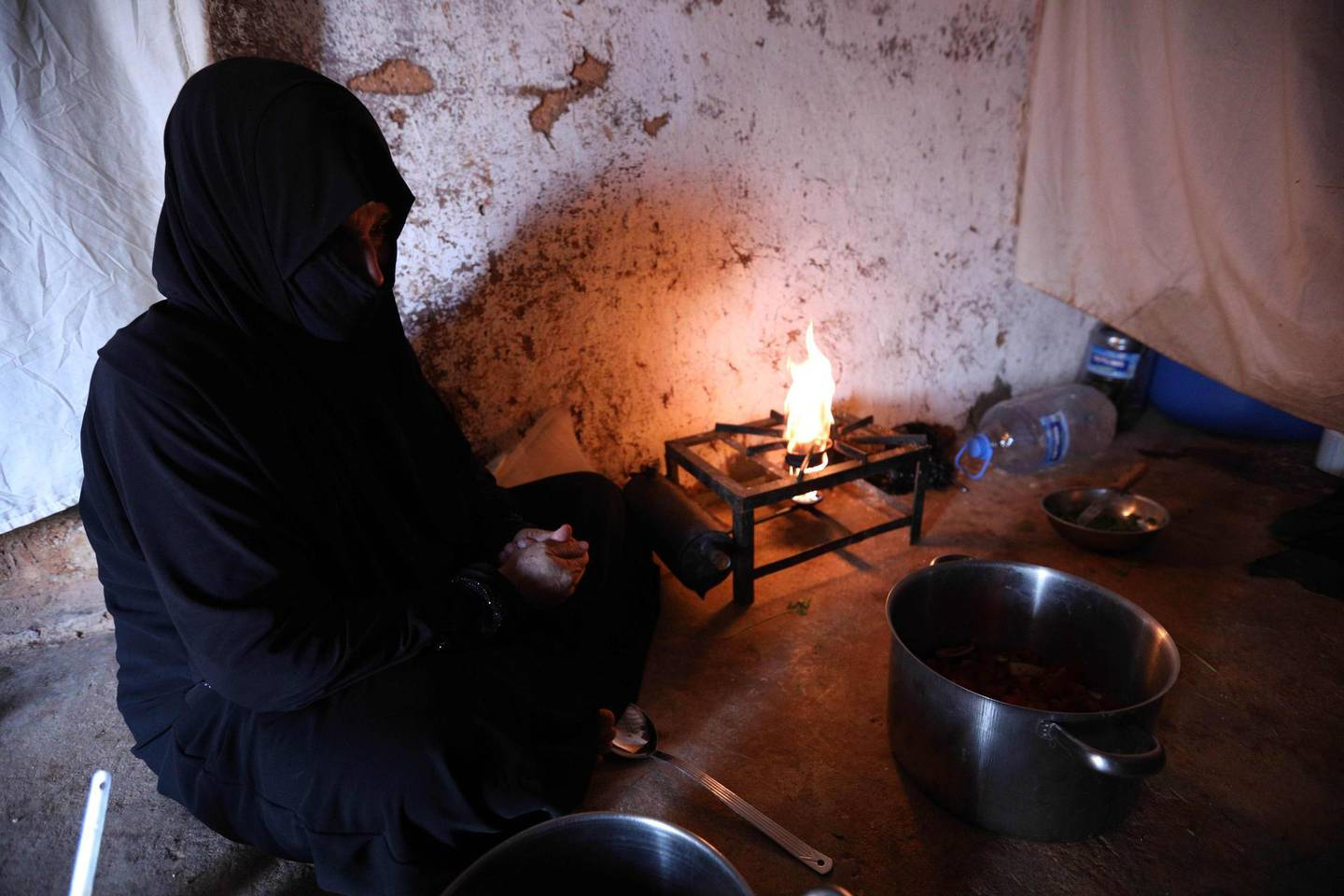 TOPSHOT - Um Samer, a displaced woman from eastern Ghouta, prepares an iftar meal at their home in Maarrat Misrin some seven kilometres north of Idlib on May 26, 2018.    / AFP / OMAR HAJ KADOUR