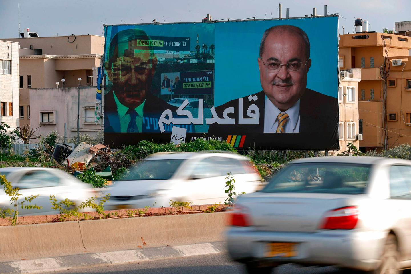 """A picture taken on February 21, 2020, shows a portrait of Arab Israeli member of the Joint List Ahmad Tibi on a campaign poster, with the Arabic writing which reads """"i am staying seated"""" in the northern Israeli City of Tayyiba.  / AFP / AHMAD GHARABLI"""