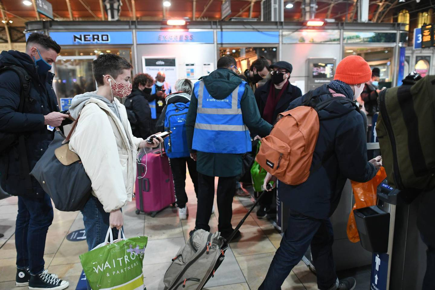 People go through barriers to catch trains at Paddington Station in London, on the last Saturday shopping day before Christmas, after the announcement that London will move into Tier 4 Covid restrictions from midnight. (Photo by Stefan Rousseau/PA Images via Getty Images)