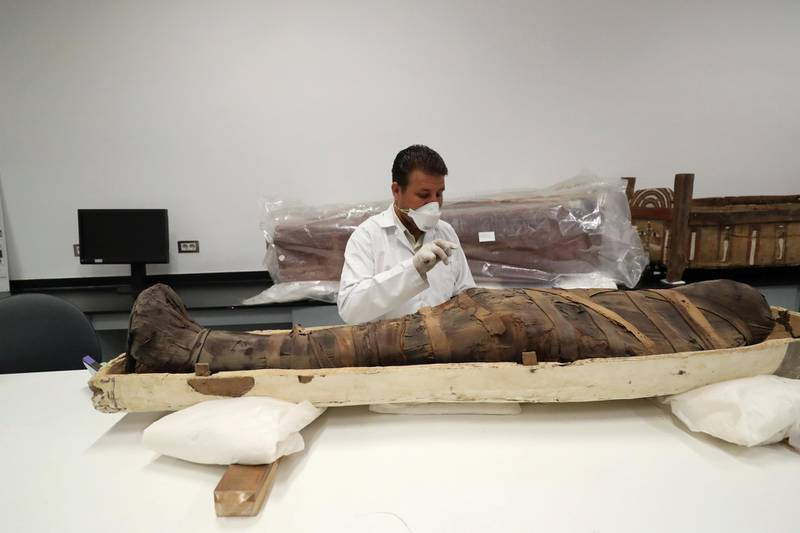 An Egyptian archaeologist check the mummy during restoration work on the coffin of King Tutankhamun at the conservation center in the Grand Egyptian Museum on August 4, 2019. - For the first time since the tomb was discovered in 1922, the coffin was transported from King Tutankhamun's tomb at the Valley of the Kings in Luxor to the Grand Egyptian Museum for an eight-month restoration process, before being displayed among his treasured collection at the museum. Tutankhamun is the formal name of the mummified pharaoh most tourists visiting Egypt's Valley of the Kings know as King Tut. (Photo by Khaled DESOUKI / AFP)