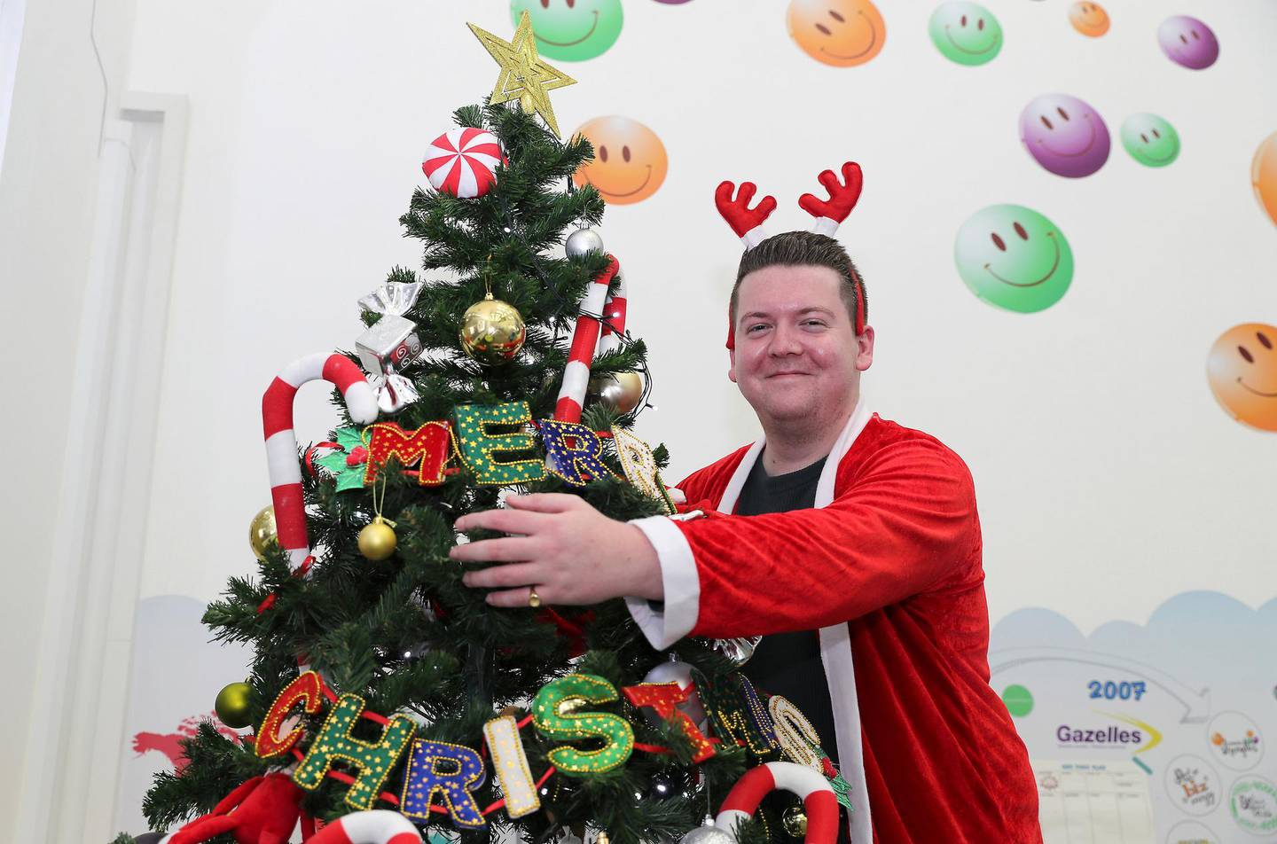 DUBAI, UNITED ARAB EMIRATES , December 16 – 2020 :- Thomas Smith, Marketing Executive with the Christmas tree at his office in the Biz group at Dubai Production City in Dubai. Thomas Smith is going to spend Christmas in Dubai and having a virtual Christmas drinks party with friends over Zoom due to pandemic and travel restrictions. ( Pawan Singh / The National ) For News/Online. Story by Gill