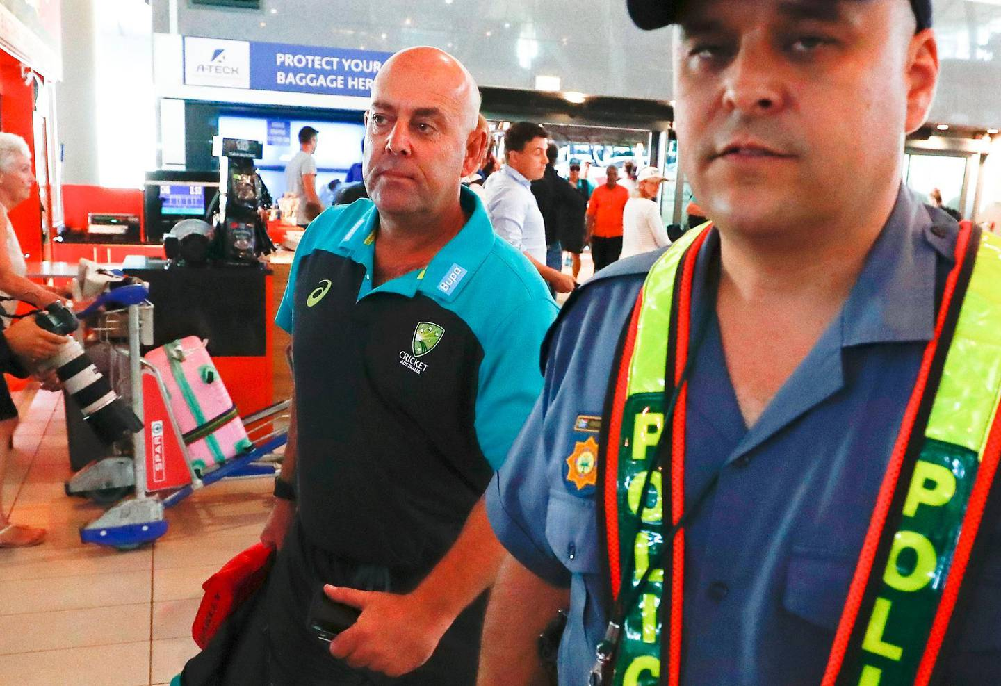 epa06631766 Australian cricket coach Darren Lehmann (L) departs from Cape Town International airport, South Africa, 27 March 2018. Australia skipper Steve Smith has been suspended by the International Cricket Council (ICC) for his part in a ball tampering scandal during the third test against South Africa. Smith admitted some senior players were aware of the ball tampering attempt. Smith and David Warner stepped down as captain and vice-captain of the Australian team in consequence to the ball meddling scandal.  EPA/NIC BOTHMA