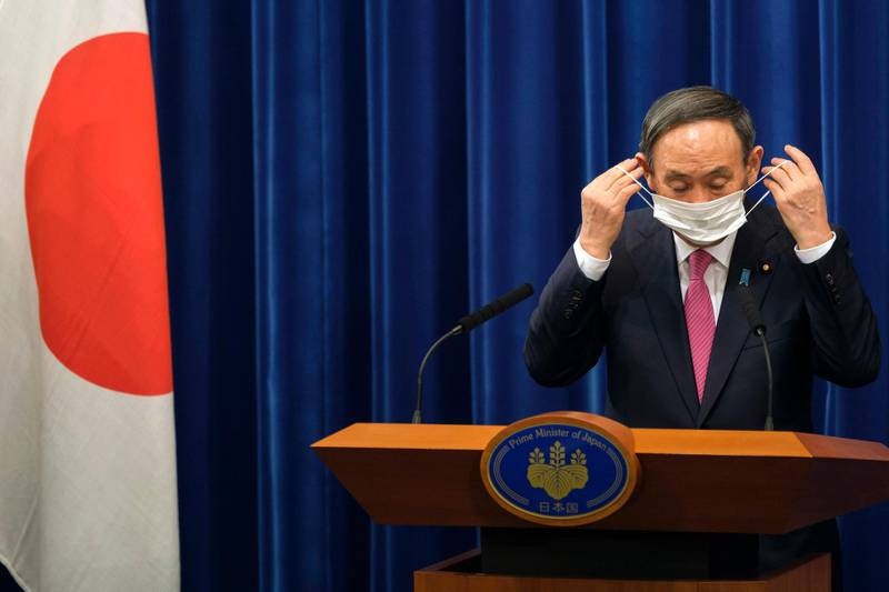 Japan's Prime Minister Yoshihide Suga puts on a face mask after a press conference on the COVID-19 situation in Japan at the prime minister's office in Tokyo, Friday, Dec. 25, 2020.  Suga on Friday he will seek a legislation to allow the government to impose legally-binding business restriction orders in return for compensation and punish violators as Japan struggles to slow the ongoing upsurge of the coronavirus cases ahead of the holiday season while people are becoming less cooperative. (Nicolas Datiche/Pool Photo via AP)