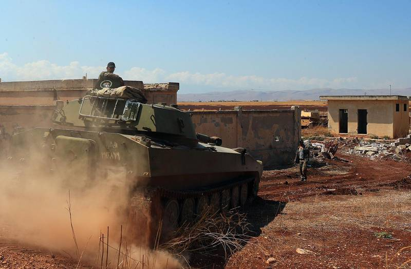 TOPSHOT - A Syrian government tank drives next to a building near the town of Khan Shaykhun in the southern countryside of the rebel-held Idlib province on August 18, 2019. A Turkish military convoy crossed into jihadist-run northwest Syria on August 19, it's path blocked by advancing regime troops as tensions soared between Damascus and Ankara, which said its forces were targeted by an air strike. / AFP / -
