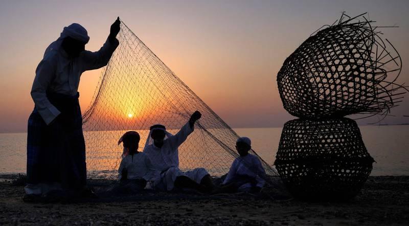 Emirati fishermen set up nets on the shore off the coast of Dalma island in the Gulf, near the Emirati capital Abu Dhabi on May 21, 2021. / AFP / Karim SAHIB