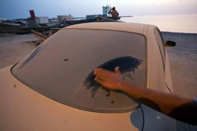 Ras al Khaimah - July 8, 2010 - One week after washing his car, this owner wipes the dust that has settled on it from the car's rear window in the village of Ghalilah, where he lives, about 25 kilometers north of Ras al Khaimah, July 8, 2010. (Photo by Jeff Topping/The National)