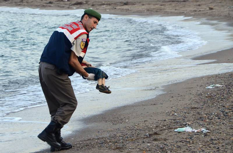 GRAPHIC CONTENT A Turkish police officer carries a migrant child's dead body (Aylan Shenu) off the shores in Bodrum, southern Turkey, on September 2, 2015 after a boat carrying refugees sank while reaching the Greek island of Kos. Thousands of refugees and migrants arrived in Athens on September 2, as Greek ministers held talks on the crisis, with Europe struggling to cope with the huge influx fleeing war and repression in the Middle East and Africa. / AFP PHOTO / DOGAN NEWS AGENCY / Nilufer Demir
