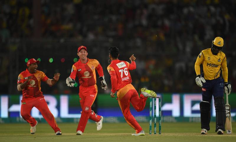 Shadab Khan (2L) of Islamabad United celebrates with teammates after taking the wicket of Darren Sammy of Peshawar Zalmi (R) during the Pakistan Super League final match between Peshawar Zalmi vs Islamabad United at the National Cricket Stadium in Karachi on March 25, 2018.  Thousands of security personnel are being deployed as Karachi hosts the final of the Pakistan Super League, its biggest cricket match in nine years, after a spate of attacks drove away foreign teams. / AFP PHOTO / ASIF HASSAN
