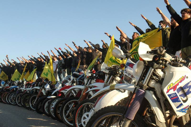 TOPSHOT - Supporters of the Lebanese Shiite movement Hezbollah perform a salute as they stand behind motorcycles carrying the group's flags in the southern Lebanese district of Marjayoun on the border with Israel on May 25, 2020. Twenty years after the withdrawal of Israeli forces from Lebanon, Hezbollah still enjoys wide support among youth regaled with tales of the Shiite group ending 22 years of Israeli occupation. / AFP / Mahmoud ZAYYAT