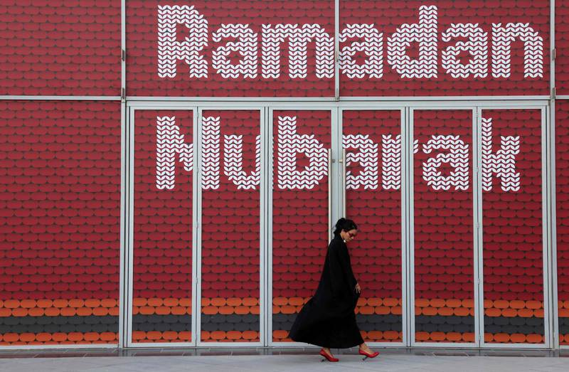 A woman walks past an installation with the message Ramadan Mubarak (blessed), on May 3, 2021 in Dubai's Design District, during the Muslim holy fasting month of Ramadan. / AFP / GIUSEPPE CACACE