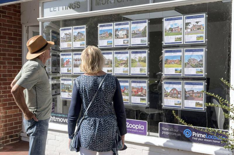 Couple looking in an estate agent's window at properties for sale. England UK. (Photo by: Education Images/Universal Images Group via Getty Images)