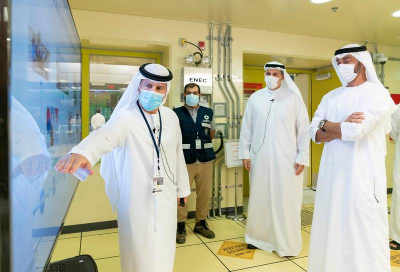 AL DHAFRA, ABU DHABI, UNITED ARAB EMIRATES - June 11, 2020: HH Sheikh Mohamed bin Zayed Al Nahyan, Crown Prince of Abu Dhabi and Deputy Supreme Commander of the UAE Armed Forces (R) views a presentation by HE Mohamed Al Hammadi, CEO Emirates Nuclear Energy Corporation (ENEC) (L), during the inspection of the Barakah Peaceful Nuclear Energy Plants, in Barakah. Seen with HE Khaldoon Khalifa Al Mubarak, CEO and Managing Director Mubadala, Chairman of the Abu Dhabi Executive Affairs Authority and Abu Dhabi Executive Council Member (2nd R).  ( Mohamed Al Hammadi / Ministry of Presidential Affairs ) ---