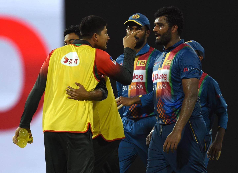 Bangladesh's Nurul Hasan (L) exchanges words with Sri Lanka's skipper Thisara Perera (R) during the sixth Twenty20 (T20) international cricket match between Bangladesh and Sri Lanka of the tri-nation Nidahas Trophy at the R Premadasa stadium in Colombo on March 16, 2018. / AFP PHOTO / ISHARA S.  KODIKARA
