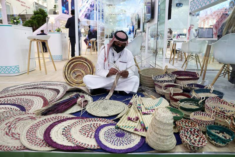 Artist making items from palm leaves at the Saudi Arabia stand during the Arabian Travel Market held at Dubai World Trade Centre in Dubai on May 16,2021. Pawan Singh / The National. Story by Deena