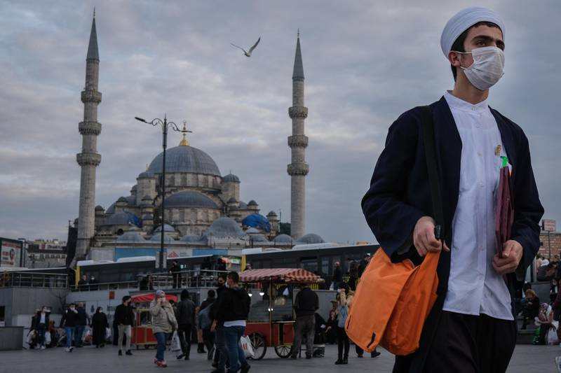 epa08926614 A man wearing face mask as he walks in front of the Yeni Mosque at the Eminonu Square  in Istanbul, Turkey, 08 January  2021. Turkey imposed curfews on weekdays after 9pm and full weekend lockdowns with the exception of tourists to combat the spread of coronavirus, after a recent spike in Covid-19 infections and related deaths.  EPA/SEDAT SUNA
