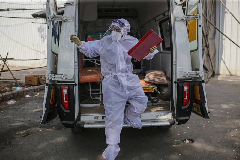 A health worker exits an ambulance outside a quarantine center at the Goregaon NESCO jumbo Covid centre in the Goregaon suburb of Mumbai, India, on Tuesday, April 27, 2021. India's spike in virus numbers has prompted state governments to impose movement curbs, which in turn have tamped down economic activity as well as stoked price pressures because of broken supply chains. Photographer: Dhiraj Singh/Bloomberg