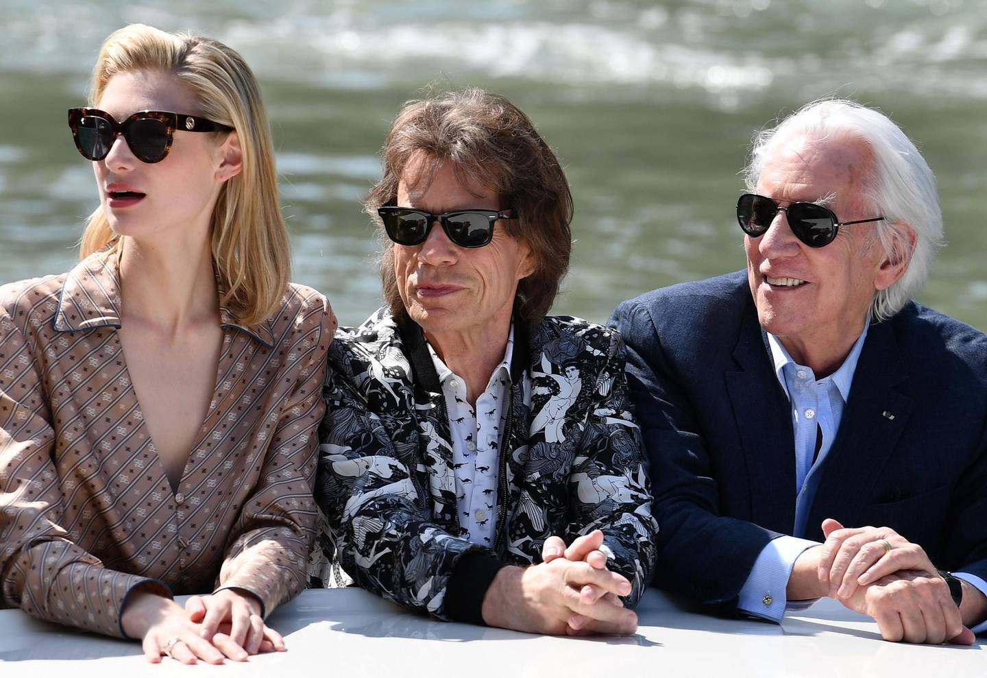 """(FromL) Australian actress Elizabeth Debicki, British musician, singer and actor Mick Jagger and Canadian actor Donald Sutherland arrive by taxi boat at the pier of the Palazzo del Casino to attend a photocall for the film """"The Burnt Orange Heresy"""" presented out of competition on September 7, 2019 during the 76th Venice Film Festival at Venice Lido.  / AFP / Alberto PIZZOLI"""