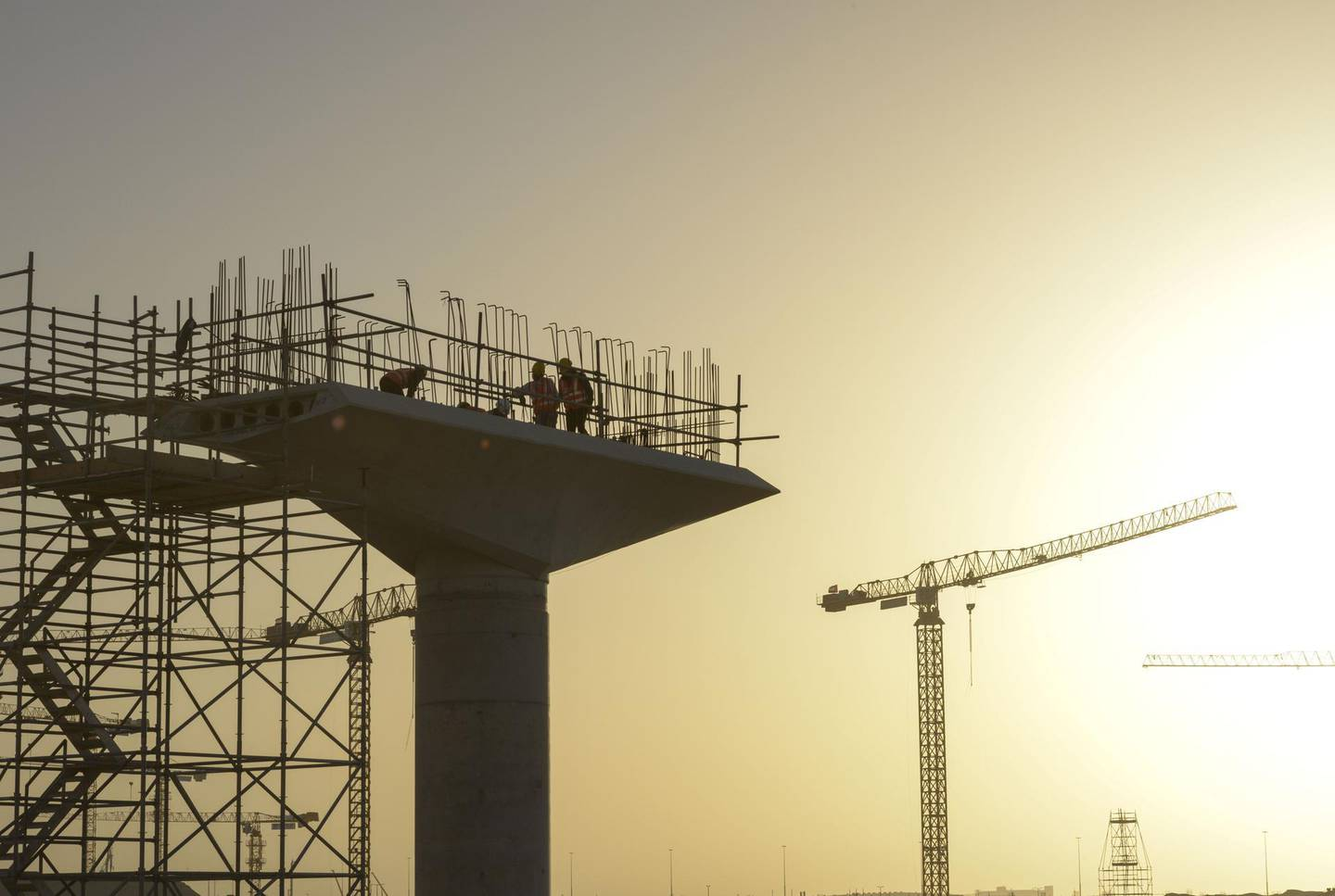 Construction workers stand on a concrete supporting structure for the new metro rail link to the city at the building site for the World Expo 2020 exhibition in Dubai, United Arab Emirates, on Tuesday, Jan. 23, 2018. Much of the Arab world is mired in violence, poverty and unemployment, and yet in Dubai they���re��busy working on sending a probe to the red planet within three years. Photographer: Khushnum��Bhandari/Bloomberg