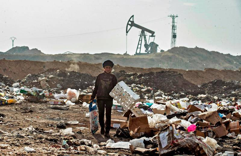 A Syrian child sifts through a garbage dump near an oil field in the countryside of Malikiya in northeast Syria, on January 12, 2021. On the dry plains outside the city of Al-Malikiyah, a dozen people wrapped up against the cold rip open the black plastic bags, in a desperate search for something to sell, repurpose or even eat. Across the road, an oil pump swings back and forth in this resource-rich region controlled by US-backed Kurdish forces.  / AFP / Delil SOULEIMAN