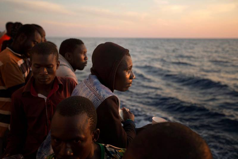 FILE - In this June 17, 2017 file photo, sub-Saharan migrants stand on the deck of the Golfo Azzurro rescue vessel. after being rescued by members of Proactive Open Arms, as they arrive at the port of Pozzallo, south of Sicily, Italy. Under a deal backed by Italy, Libya��������s struggling government in Tripoli has paid militias that were once involved in smuggling migrants to now prevent migrants from crossing the Mediterranean to Europe, one reason for a dramatic drop in the traffic, according to militia and security officials. (AP Photo/Emilio Morenatti, File)