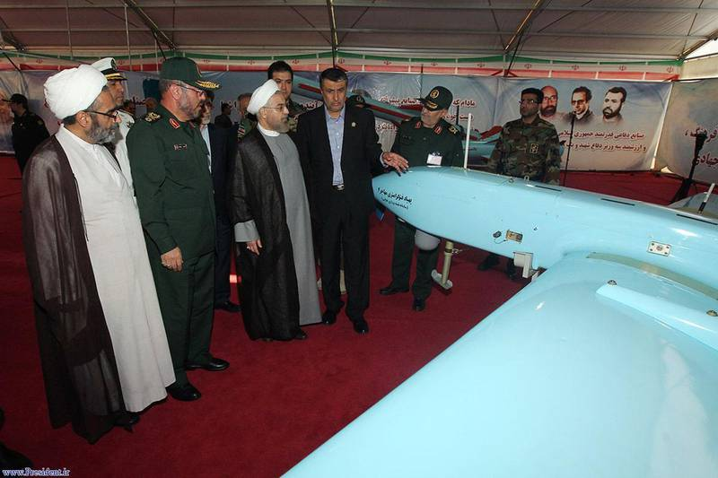 """A handout picture released by the official website of the Iranian President, shows  president Hassan Rouhani (C) visiting a display of  Iran's drone, Mohajer 4, as part of Iran's defence capabilities exhibition inside the defence ministry building in Tehran on August 24, 2014. The foreign minister of Iran, which is aiding Iraq in its fight against jihadist-led militants, visited Baghdad, as gunmen made a renewed push for the country's main oil refinery. AFP PHOTO/HO/ IRANIAN PRESIDENCY WEBSITE   == RESTRICTED TO EDITORIAL USE - MANDATORY CREDIT """"AFP PHOTO / HO/ IRANIAN PRESIDENCY WEBSITE """" - NO MARKETING NO ADVERTISING CAMPAIGNS - DISTRIBUTED AS A SERVICE TO CLIENTS == (Photo by HO / IRANIAN PRESIDENCY WEBSITE / AFP)"""