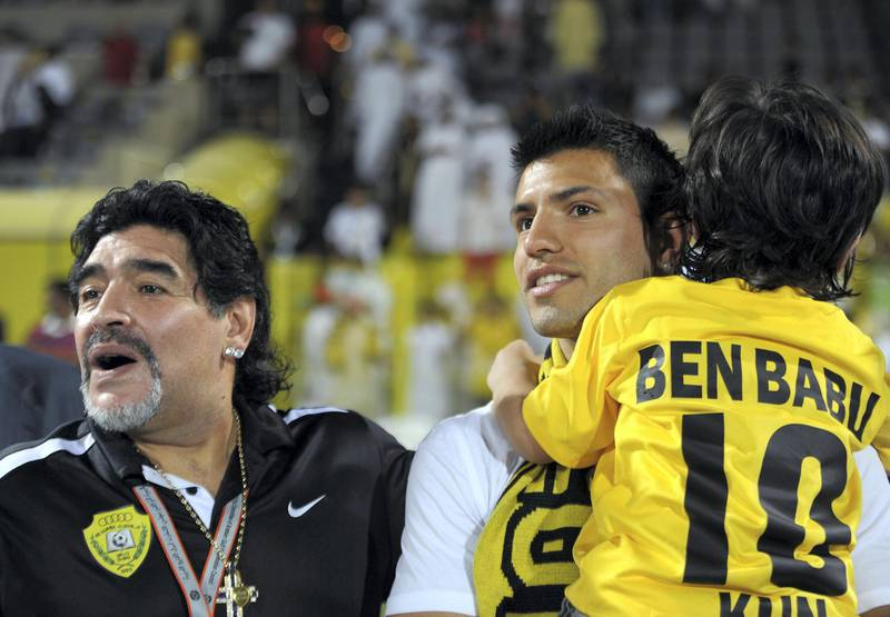 Al-Wasl club's Argentinian head coach Diego Maradona (L) stands with his son in law, Manchester City's Sergio Aguero (C), and his grandson Benjamin at the end of a Gulf Cooperation Council Champions League football match between Al-Wasl and Al-Wehda clubs in Dubai on May 15, 2012. AFP PHOTO/STR (Photo by - / AFP)