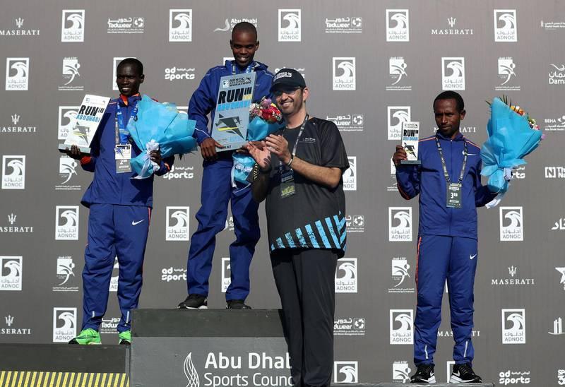 Abu Dhabi, United Arab Emirates - December 06, 2019: Dr Sultan Al Jaber presents the 1st, 2nd 3rd to Joel Kemboi Kimurer (L, 2nd), Reuben Kipyego (m, winner) and Fikadu Teferi Girma (L, 3rd) for the mens ADNOC Abu Dhabi marathon 2019. Friday, December 6th, 2019. Abu Dhabi. Chris Whiteoak / The National