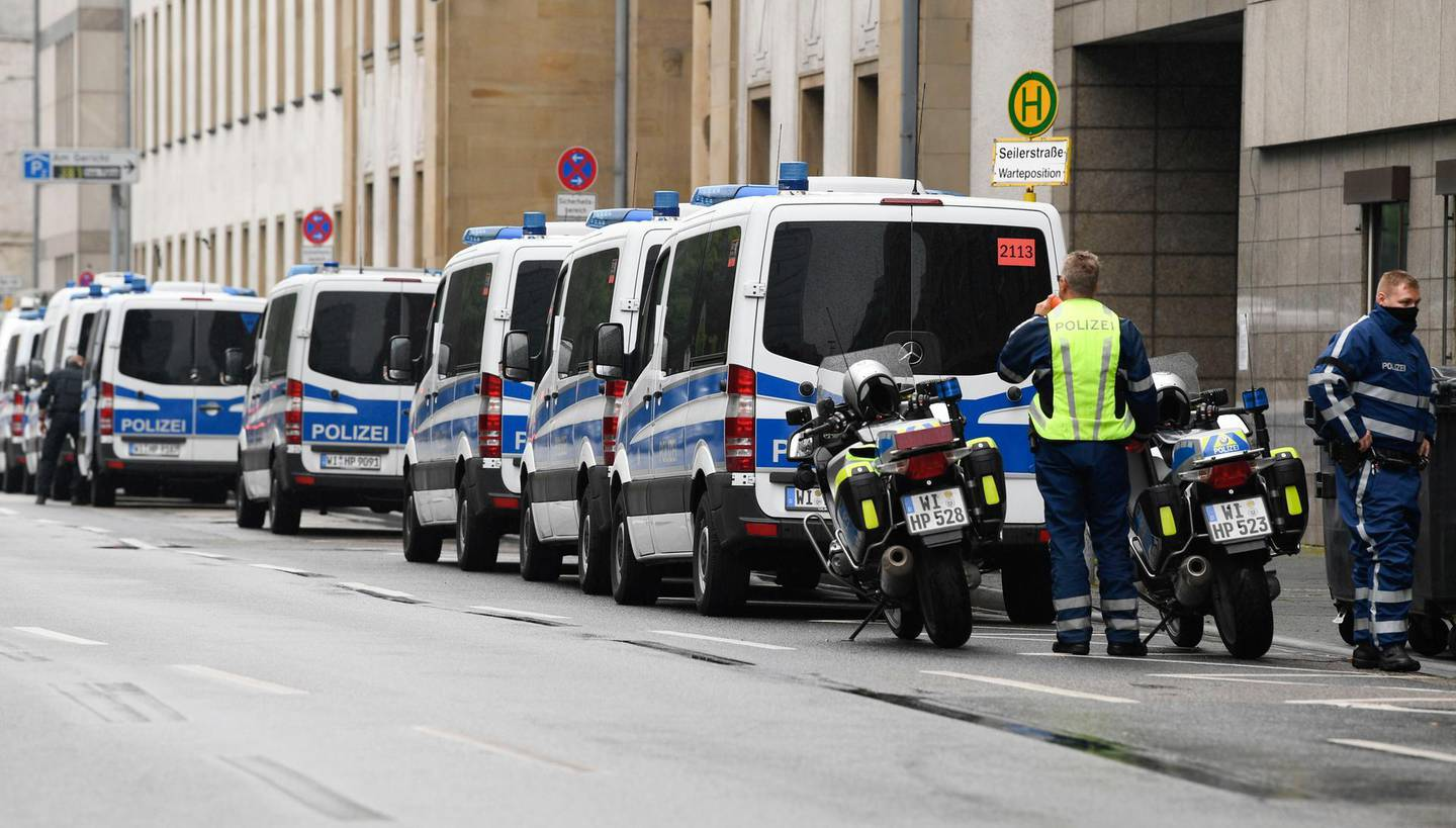 """Police vehicles are lined up along the Higher Regional Court in Frankfurt am Main on June 16, 2020 for the start of the trial of the accused of killing politician Walter Luebcke, who belonged to Chancellor Angela Merkel's conservative CDU party and headed the Kassel regional council in the western state of Hesse. A German neo-Nazi stands trial Tuesday on charges of murdering pro-refugee politician Walter Luebcke, in a case that shocked the country and highlighted the growing threat of right-wing extremism. Federal prosecutors believe the main suspect, 46-year-old Stephan E, was motivated by """"racism and xenophobia"""" when he allegedly drove to Luebcke's house on June 1, 2019 and shot him in the head. / AFP / THOMAS KIENZLE"""