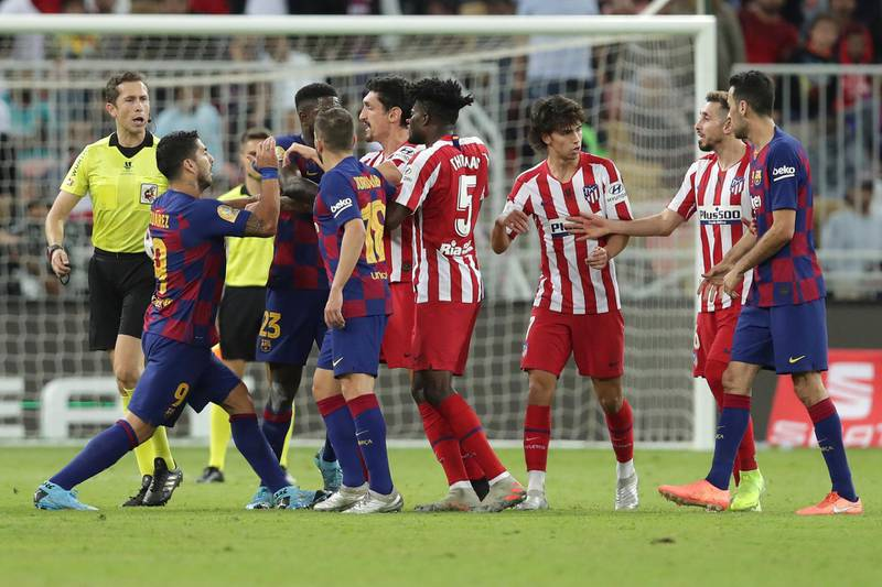 Barcelona's Luis Suarez, left, fights with Atletico Madrid's Stefan Savic, center, during the Spanish Super Cup semifinal soccer match between Barcelona and Atletico Madrid at King Abdullah stadium in Jiddah, Saudi Arabia, Thursday, Jan. 9, 2020. (AP Photo/Hassan Ammar)