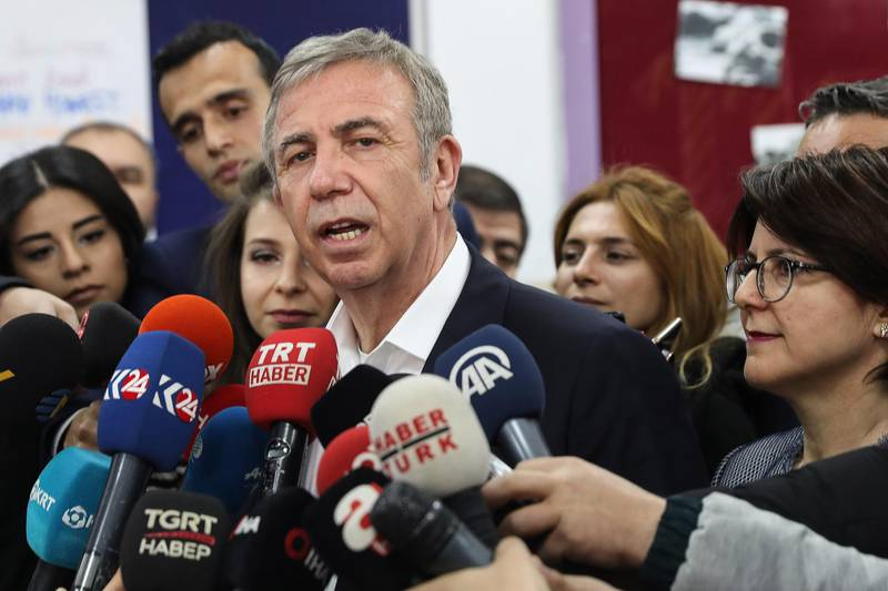 (RMayoral candidate of the main opposition Republican Peoples Party (CHP) Mansur Yavas (C) speaks to the press, next to his wife Nursen Yavas (R), at a polling station during the local elections in Ankara, on March 31, 2019. - Turkish voters go to the polls on March 31 for 30 major cities, 51 provincial municipalities and district councils. The vote will be a barometer on how well the AKP is faring after building its ballot box success on Turkey's growth. (Photo by Adem ALTAN / AFP)