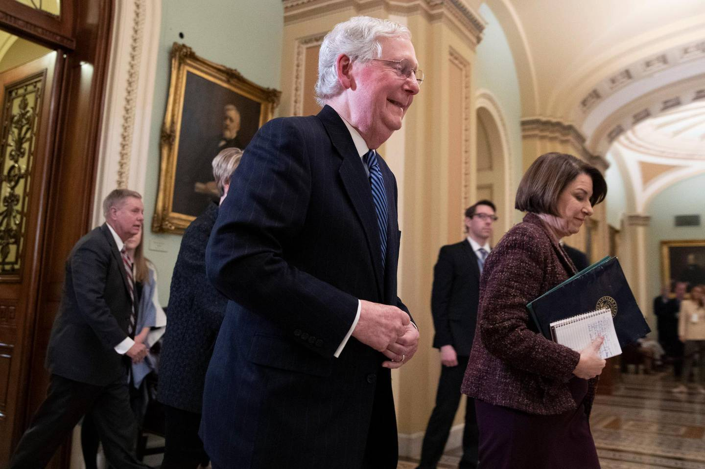Senate Majority Leader Mitch McConnell, R-KY., walks out of the Senate chamber with Sen. Amy Klobuchar, D-Minn., during a break in the impeachment trial of President Donald Trump at the Capitol, Wednesday, Jan. 22, 2020, in Washington. (AP Photo/Steve Helber)
