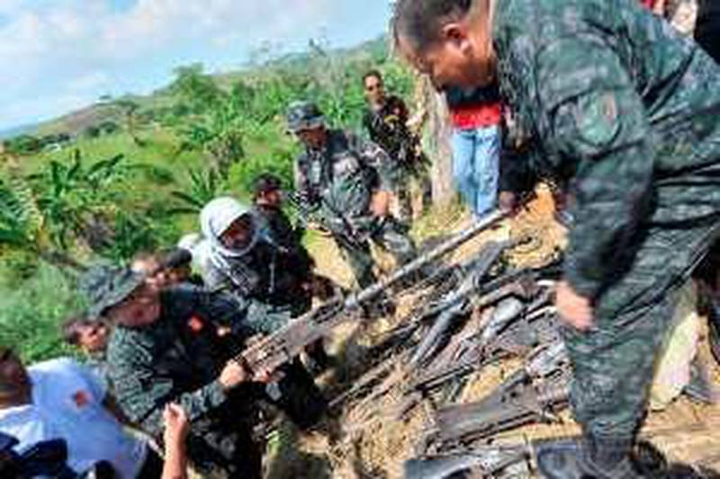 CORRECTION Police officials shows a .50 caliber machine gun unearthed along with a cache of weapons at a property believed to be owned by the governor of Maguindanao in Datu Hoffer on the outskirts of the provincial capital, Shariff Aguak, in the southern Philippine province of Maguindanao on December 6, 2009.  About 40 firearms, including M16 assault rifles, were uncovered on the property that is believed to be owned by the governor of Maguindanao province, Andal Ampatuan Sr., military spokesman Lieutenant Colonel Michael Samson told AFP at the site.    AFP PHOTO / TED ALJIBE