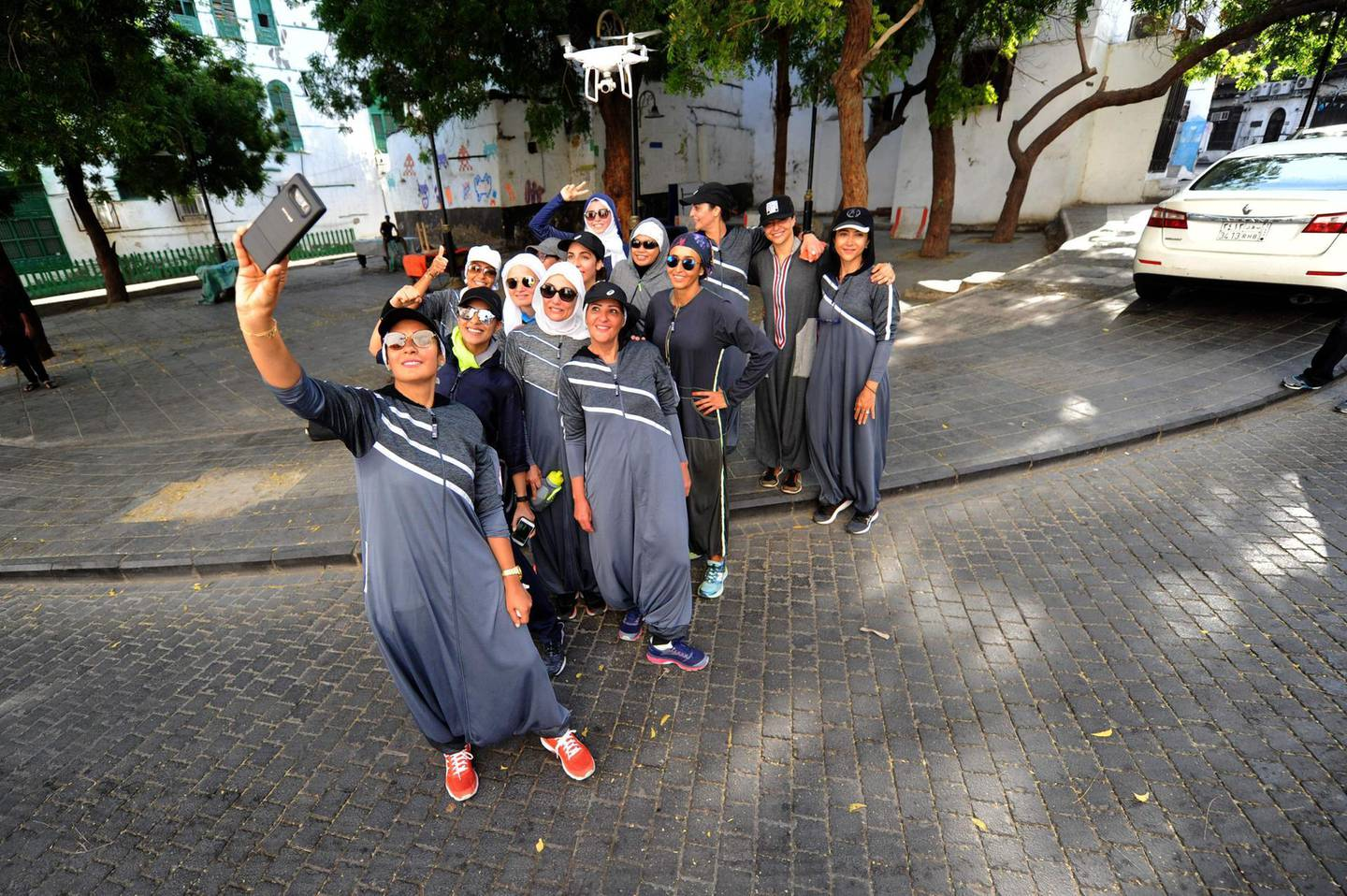 Saudi women pose for a selfie after a jog in the streets of Jeddah's historic al-Balad district on March 8, 2018. Colourful and oozing defiance, a sports-friendly version of the abaya gown was once considered a symbol of cultural rebellion in conservative Saudi Arabia, but it is fast becoming the new normal. / AFP PHOTO / Amer HILABI