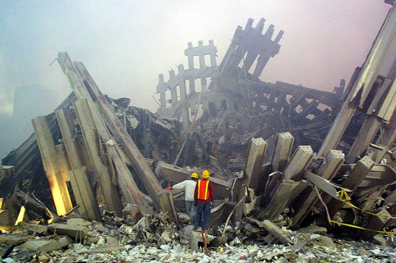 Rescue workers survey damage to the World Trade Center 11 September, 2001 in New York. Two planes controlled by hijackers crashed into the twin towers of the center destroying the buildings. At almost the same time, another hijacked plane flew into the Pentagon in Washington, DC.  AFP PHOTO Doug KANTER (Photo by DOUG KANTER / AFP)