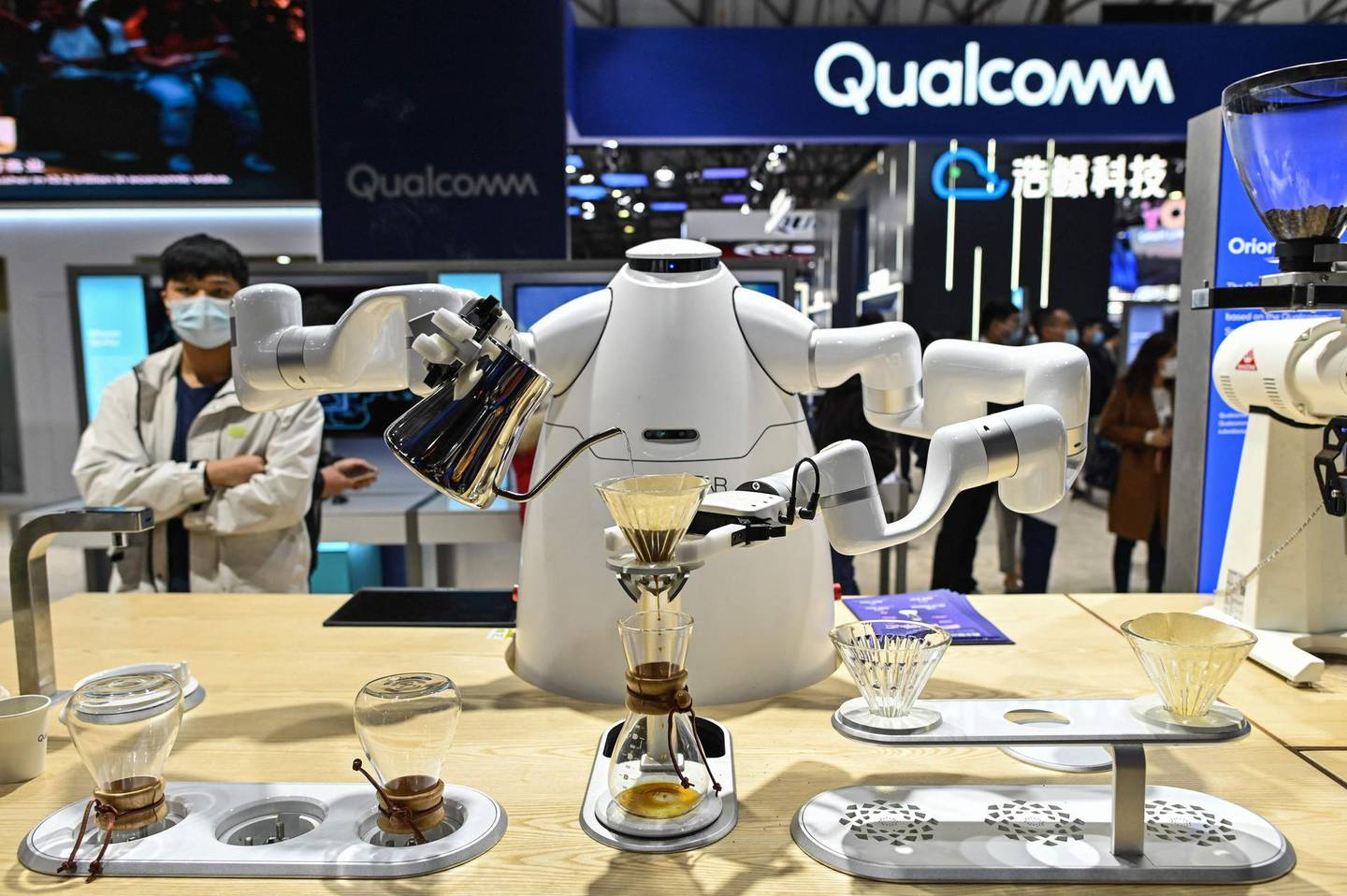 A robot prepares a coffee at a booth during the Mobile World Congress in Shanghai on February 23, 2021.  / AFP / Hector RETAMAL