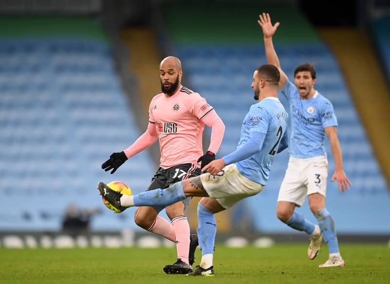 MANCHESTER, ENGLAND - JANUARY 30: Kyle Walker of Manchester City passes past David McGoldrick of Sheffield United during the Premier League match between Manchester City and Sheffield United at Etihad Stadium on January 30, 2021 in Manchester, England. Sporting stadiums around the UK remain under strict restrictions due to the Coronavirus Pandemic as Government social distancing laws prohibit fans inside venues resulting in games being played behind closed doors. (Photo by Michael Regan/Getty Images)
