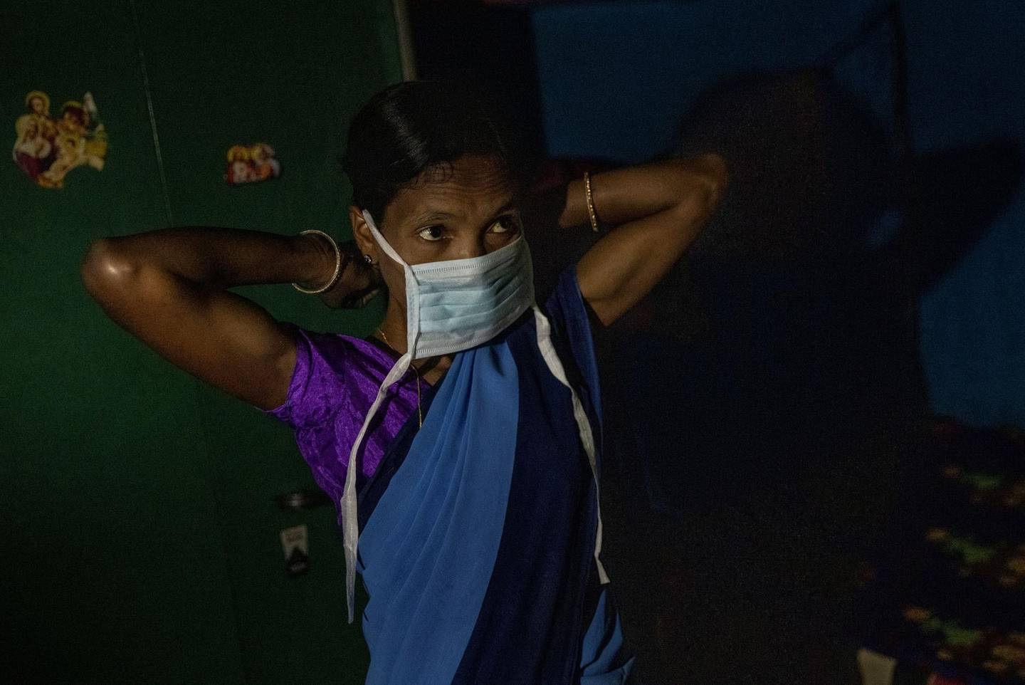 """Reena Jani, 34, a health worker, puts on a protective face mask as she gets ready to travel to Mathalput Community Health Centre to receive the vaccine developed by Oxford/AstraZeneca, during the coronavirus disease (COVID-19) pandemic, in Pendajam village in Koraput, India, January 16, 2021. Jani became an accredited social health activist (ASHA) community health worker, a lynchpin of India's rural healthcare system, around seven years ago. She helps to monitor pregnant women in her village of 500 people, and helps with malaria tests and doles out basic medication for fever and diarrhoea. The main breadwinner for her family of five, Jani draws a monthly salary of 3,000 rupees ($41), helping put her two daughters and one son through school. When she first learned she was to be vaccinated, Jani said she wasn't worried. Then she heard a rumour. """"Someone told me that people are fainting, they are developing fever and some are dying after taking the injection,"""" she said. """"That is why I was frightened."""" REUTERS/Danish Siddiqui     SEARCH """"SIDDIQUI OXFORD/ASTRAZENECA"""" FOR THIS STORY. SEARCH """"WIDER IMAGE"""" FOR ALL STORIES"""