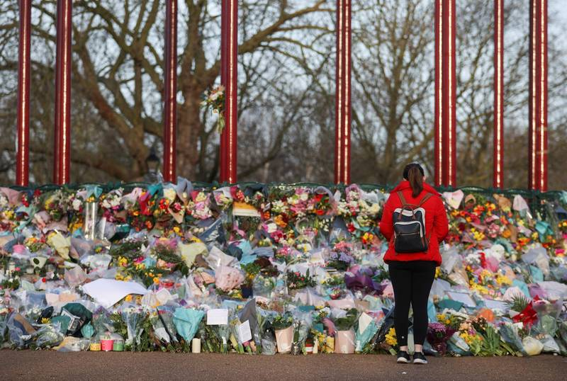 A woman looks at flowers at a memorial site at the Clapham Common Bandstand, following the kidnapping and murder of Sarah Everard, in London, Britain, March 17, 2021. REUTERS/Hannah McKay