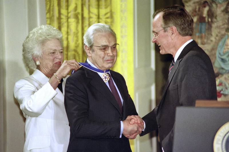 """Outgoing UN Secretary General Javier Perez de Cuellar (C) receives the Presidential Medal of Freedom from US President George Bush (R) and First Lady Barbara Bush during a ceremony in the White House on December 12, 1991. - De Cuellar was cited for """"ten years of exceptionally distinguished service"""". (Photo by Paul J. RICHARDS / AFP)"""