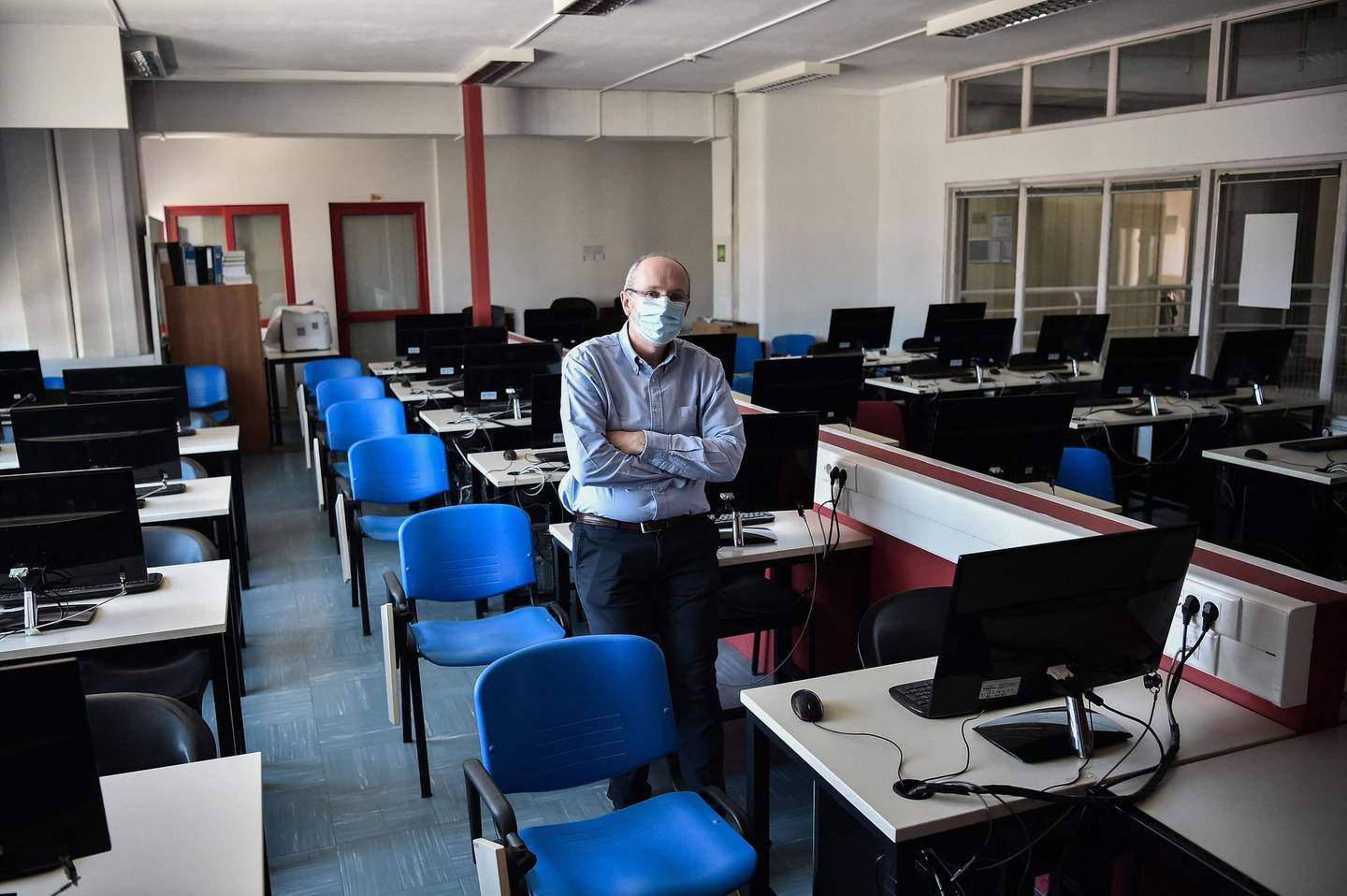 Alexandros Chatzigeorgiou, Dean and Professor of the Department of Applied Informatics poses for a photograph in a classroom in the University of Macedonia, in Thessaloniki on April 15, 2021. Shuttered for over a year due to the Covid-19 pandemic, Greek universities are now grappling with a surge in online exam cheating giving rise to a new reality: the 'Corona degree'. Both professors and students admit that examination safeguards are practically impossible to enforce in a remote learning environment with hundreds of participants simultaneously online. / AFP / Sakis MITROLIDIS
