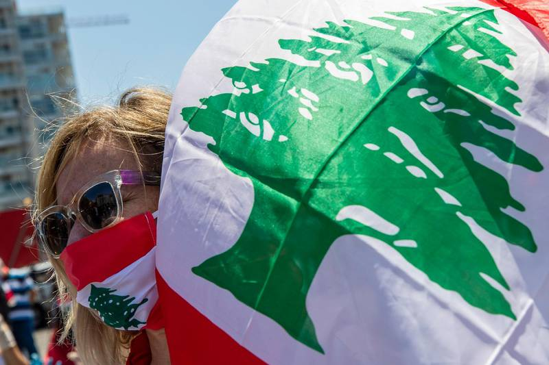 An anti-government protester while wears a mask with the colors of the Lebanese flag to help curb the spread of the coronavirus, during a May Day protest near the Lebanese Central Bank in Beirut, Lebanon, Friday, May 1, 2020. Hundreds rallied outside the country's central bank and in other parts of the country a day after the prime minister said he'll be seeking a rescue program from the International Monetary Fund to deal with a spiraling economic crisis. (AP Photo/Hassan Ammar)