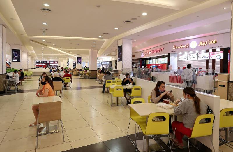 DUBAI, UNITED ARAB EMIRATES , April 29 – 2020 :- People having food inside the food court at Mall of the Emirates. Authorities ease the restriction for the residents in Dubai. At present mall opening timing is 12:00 pm to 10:00 pm. Carrefour timing is 9:00 am to 10:00 pm. Barricades put up around the food court area during the Ramadan. (Pawan Singh / The National) For News/Standalone/Online. Story by Patrick