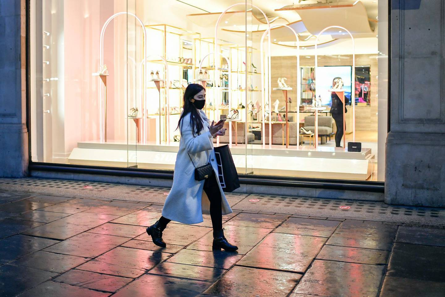 A woman wears a face mask as she walks in Regent Street, ahead of the new Tier-4 restriction measures, in London, Saturday, Dec. 19, 2020. Britain's Prime Minister Boris Johnson says Christmas gatherings cannot go ahead and non-essential shops must close in London and much of southern England as he imposed a new, higher level of coronavirus restrictions to curb rapidly spreading infections.(AP Photo/Alberto Pezzali)