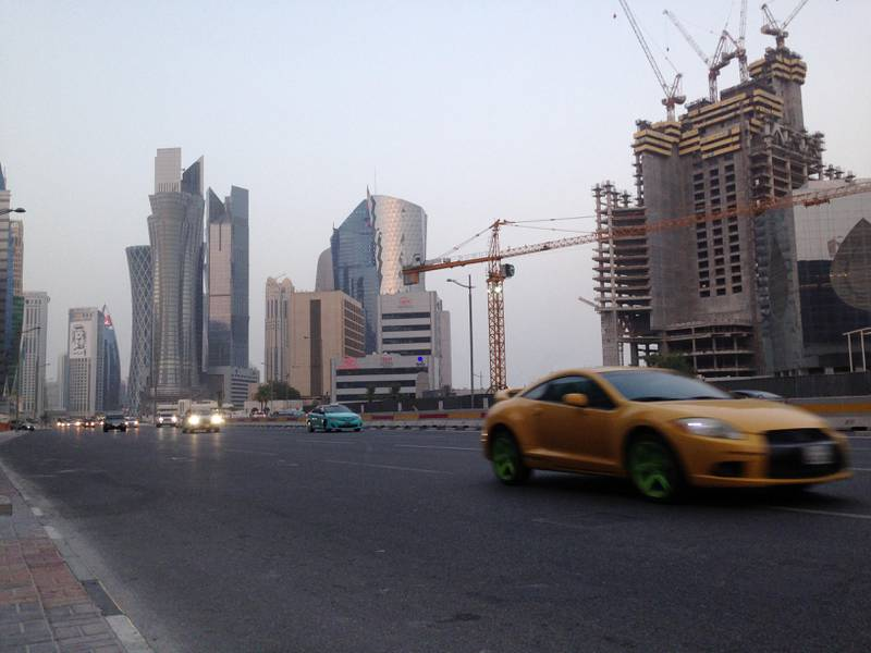FILE - In this Monday, July 10, 2017 file photo, a sports car drives through downtown Doha. It's been more than a month since four Arab nations cut land, sea and air routes to Qatar, but in the gas-rich Gulf nation's glimmering malls and luxury hotels there is little sign of hardship. (AP Photo/Maggie Hyde, File)
