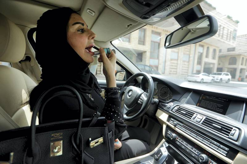 Enaam Gazi al-Aswad, 43, one of the first female drivers hired by the ride sharing company Careem but waiting for Saudi license to be issued by the government, applies lipstick inside her car at a company's office in Jeddah, Saudi Arabia June 24, 2018. Picture taken June 24, 2018. REUTERS/Zohra Bensemra