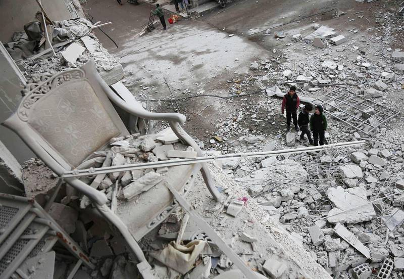 """CORRECTION - Syrian children look at a building that was damaged in a missile attack on the rebel-held besieged town of Arbin, in the eastern Ghouta region on the outskirts of the capital Damascus, on January 18, 2018.  / AFP PHOTO / ABDULMONAM EASSA / """"The erroneous mention[s] appearing in the metadata of this photo by ABDULMONAM EASSA has been modified in AFP systems in the following manner: [on the rebel-held besieged town of Arbin, in the eastern Ghouta region on the outskirts of the capital Damascus] instead of [isolated Kurdish enclave of Afrin in northern Syria]. Please immediately remove the erroneous mention[s] from all your online services and delete it (them) from your servers. If you have been authorized by AFP to distribute it (them) to third parties, please ensure that the same actions are carried out by them. Failure to promptly comply with these instructions will entail liability on your part for any continued or post notification usage. Therefore we thank you very much for all your attention and prompt action. We are sorry for the inconvenience this notification may cause and remain at your disposal for any further information you may require."""""""