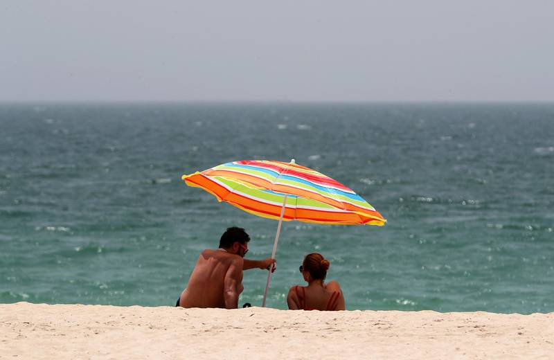 DUBAI, UNITED ARAB EMIRATES , June 27 – 2020 :- Visitors during the hot and humid weather at the Kite beach in Dubai. (Pawan Singh / The National) For Standalone